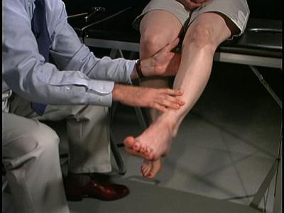 Fotografia que mostra médico examinando força motora do quadríceps.